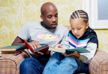 father and son reading books on chair